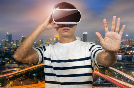 night vision: Double exposure, man wearing virtual reality goggles, night city.
