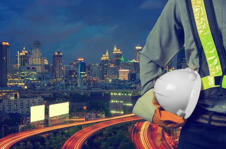 ingenieria industrial: Engineer holding awhite helmet for the safety of the workers, with expressway as a backdrop and modern building in the business district twilight time.