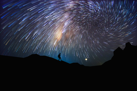 Silhouette of man with backpack on hill watching the stars at night, long exposure.