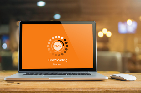 Laptop on table with Downloading bar load waiting on digital display,  indicator concept. Stock Photo