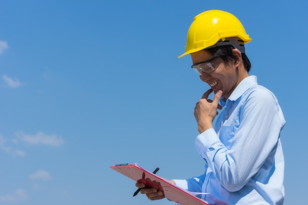 Ingenieursglimlach gele helm dragen en controlelijst die. Stockfoto - 80017983