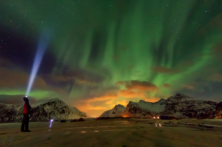 Aurora borealis above snowy islands of Lofoten.