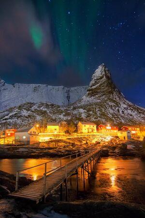 auroral: Aurora borealis (Polar lights) over Hammarskaftet, an amazing bit of rock situated close to the village of Reine - Lofoten islands, Norway