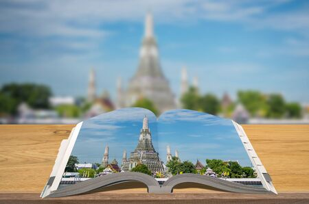 Creativity guidebooks travel, Open book on wooden table with blurred nature background, Scene Wat Arun. Stock Photo