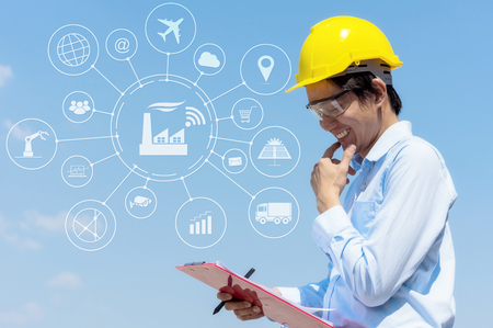 Engineer smile wearing yellow helmet and checklist with icon industry. Stock Photo