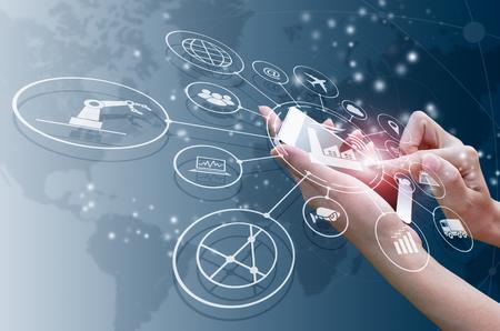 Koncepcja Przemysłu 4.0, inteligentna fabryka z kontrolą przez Internet. Użyj smartfona, aby sprawdzić status i zamówienie, z automatyzacją przepływu ikon i wymianą danych w technologiach produkcyjnych. Zdjęcie Seryjne