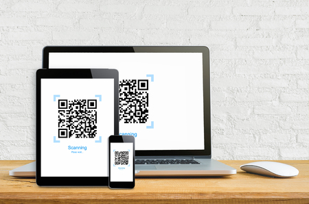 Laptop smartphone and tablet mockup with Realistic QR code on white wall, gadget and bar code information. Фото со стока