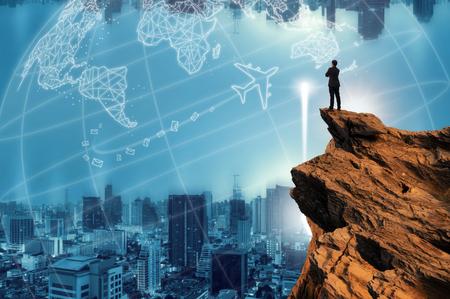 Vision conceptuelle, homme d'affaires portant une veste de costume décontractée confortable, étreinte de la poitrine au sommet du pic de la montagne et regardant vers l'avant avec fond de paysage urbain, succès, concurrence et concept de leader.