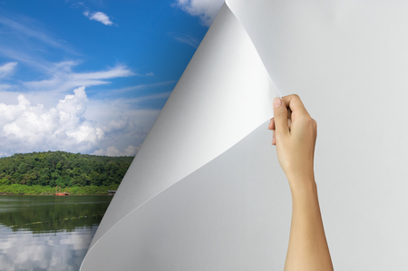 Change concept, Woman hand turning blank paper page revealing nature landscape, changing reality, hope inspiration,environmental protection, change weather, environmental campaign.