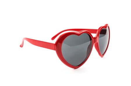 Red heart shaped sunglasses isolated on white background, summer holidays, valentines day, travel. Stock Photo