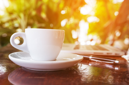 A cup of hot white coffee on the desk in the morning coffee shop. Stock Photo