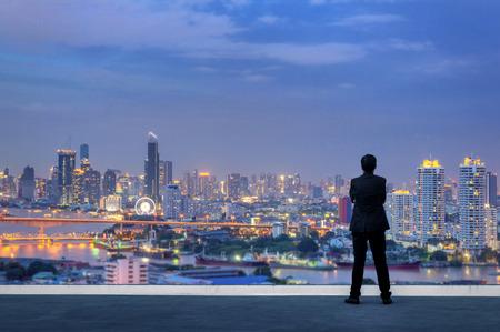 Visie concept. Succesvolle zakenman permanent met handen gekruist op de borst, bovenop het gebouw en kijkt door Cityscape Skyline Night Light. Stockfoto