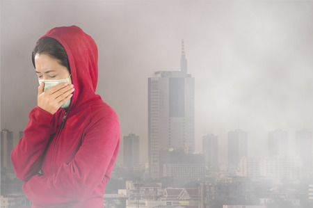 "Woman with flu sneezing, woman dressed pink in winter clothing wearing mask to her nose in a cold and flu health concept against ""Toxic dust"" covered the city of Bangkok has a health effect."