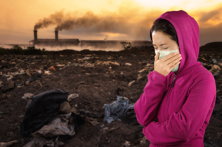 Woman with flu sneezing, woman dressed pink in winter clothing wearing mask to her nose in a cold and flu health concept against air pollution background.