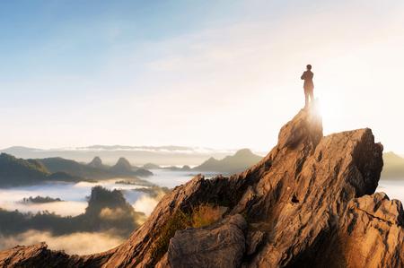 Visión conceptual, joven empresario vistiendo un cómodo traje casual, chaqueta de pie, abrazo en el pecho en la cima de la montaña pico y mirando hacia el futuro, el éxito, la competencia y el concepto de líder. Foto de archivo