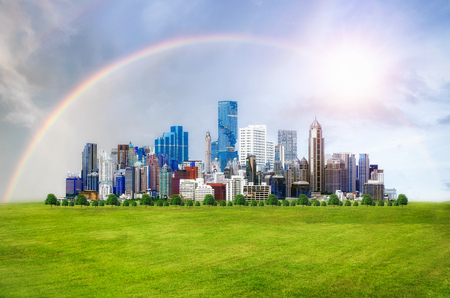 Modern city view with beautiful buildings on green grass, rainbow on sky and the sun, Green city concept.