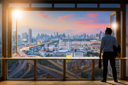 Concept vision, Young businessman wearing comfortable casual suit jacket standing holding a work bag in Working room near the glass window and looking through the modern buildings in the skyline. Zdjęcie Seryjne - 107416194