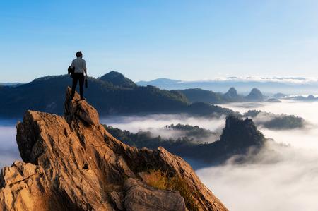 Konzeptvision, junger Geschäftsmann, der bequeme lässige Anzugjacke trägt, die Geschäftstasche auf dem Gipfelberg hält und nach vorne, Erfolg, Wettbewerb und Leitkonzept schaut.