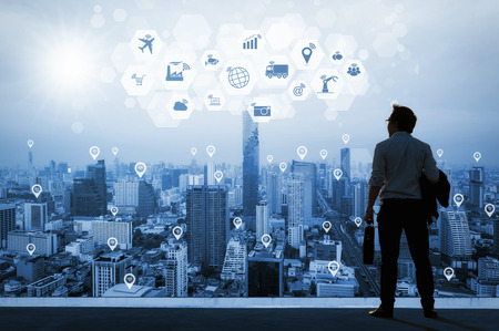 Vision concept, Young business man on the roof of the building and look through to find out goals and success with technology internet of thing and network wifi, ambition and commitment to success.