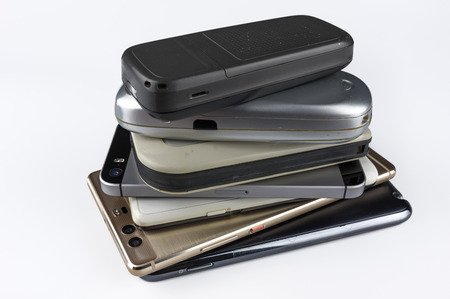 Stack of high-end smartphones on white desk.