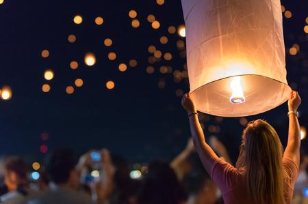 Vrouwen geven drijvende lantaarns vrij op het Loy Krathong-festival of het drijvende lantaarnsfestival in Chiang Mai, Thailand.