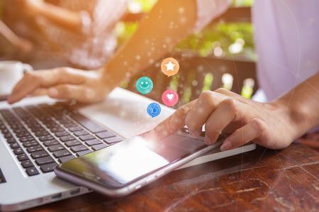Donna mano premendo su smart phone con faccina sorridente, come, amore e star emoticon sul touch screen virtuale. Concetto di valutazione del servizio clienti. Archivio Fotografico