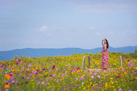 Beautiful woman in nature flower, Her wear white dresses and red hat in Tung Bua Tong Mexican sunflower field in Mae Moh Coal Mine, Lampang Province, Thailand.