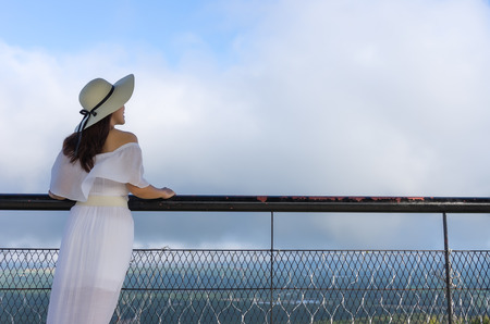 Beautiful woman wearing white dress posing on viewpoint of coal power plant mae moh, Lampang Thailand. She seeing the scenery.
