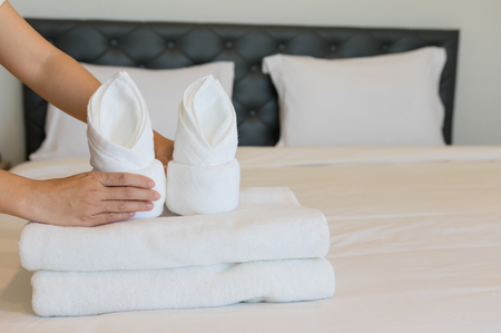Young hotel maid putting soft towels, bedding and towels in a hotel cleaner was placed on a clean white blanket on the bed with a pillow in the bedroom the morning. Imagens