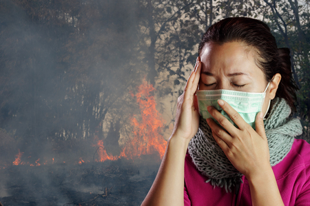 Asian women wear masks to prevent air pollution with background Wildfire burning tree in red and orange color at afternoon in the forest along smoke and flames.