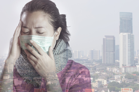 Asian women wear masks to prevent air pollution with background against