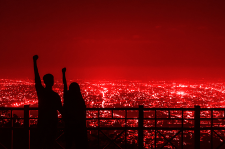 The silhouette of the couple holding hands to express their joy at the Chiang Mai city night view point.