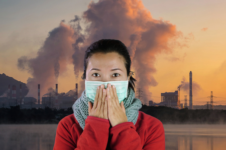 Asian women wear masks to prevent air pollution with background smoke on air form industrial. Stock Photo