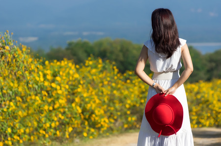 A beautiful woman in white dress and red hat in nature, in rural road, standing back, spring, sunset, on Tung Bua Tong Mexican sunflower field in Mae Moh Coal Mine, Lampang Province, Thailand. Banco de Imagens