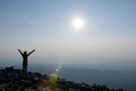 Silhouette of Young woman standing on top of cliff in summer mountains at sunset and enjoying view of nature viewpoint of the knob stone ground, Phu Hin Rong Kla National Park, Leadership Concept.