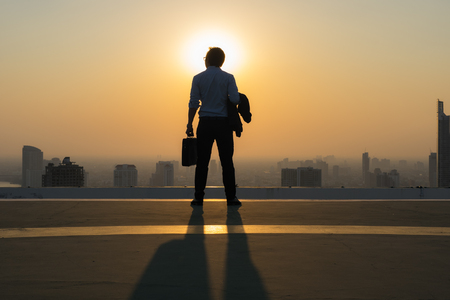 Concept vision, Young businessman wearing comfortable casual suit jacket standing holding a work bag on top of the building and looking over tall modern building, Cityscape Skyline, Vision business. Banque d'images