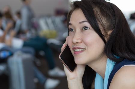 여성 승객은 비행기 여행을 기다리는 공항 승객 라운지의 대기실에 앉아 있습니다. 그녀는 스마트폰을 사용하면서 웃고 있다.
