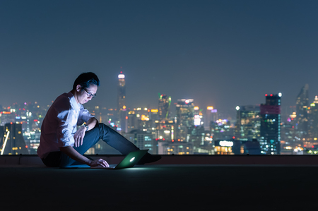 Asian businessman sitting at the top of the building. Use the laptop computer with the scenery of the night view of the city, Business success and technology concept. Imagens - 122119096