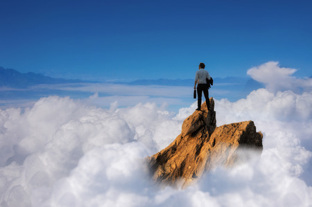 Success concept, Businessman standing on top of peak mountain cliff over the clouds  and looking forwards, competition and leader concept. Фото со стока