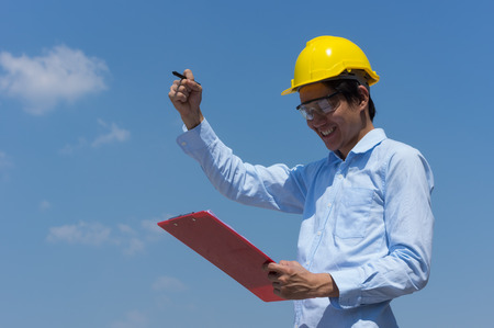 Ingenieurlächeln mit gelbem Helm und Checkliste. Standard-Bild