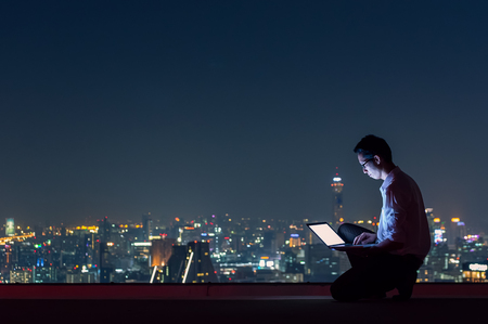 Asian businessman sitting at the top of the building. Use the laptop computer with the scenery of the night view of the city, Business success and technology concept.