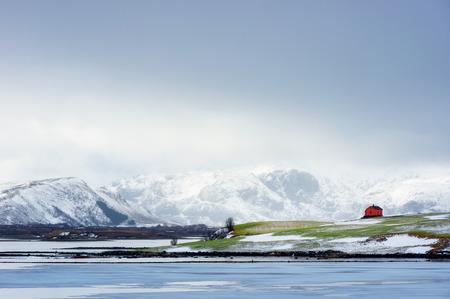 The  beautiful distinctive red house on the green lawn, view of scenic Lofoten Islands archipelago winter scenery, Beautiful mountain landscape in winter Norway, Scandinavia.