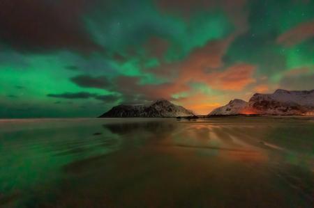 Hermosa vista del pintoresco paisaje invernal del archipiélago de las islas Lofoten, con auroras boreales o auroras boreales, hermoso paisaje de montaña en invierno Noruega, Escandinavia. Foto de archivo