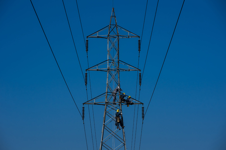 Maintenance staff on high voltage poles, Electrician or engineer works on power post and high voltage system for maintenance. High-power distribution system is damaged.