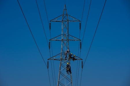 Onderhoudspersoneel op hoogspanningspalen, elektricien of ingenieur werkt aan elektriciteitspost en hoogspanningssysteem voor onderhoud. High-power distributiesysteem is beschadigd.