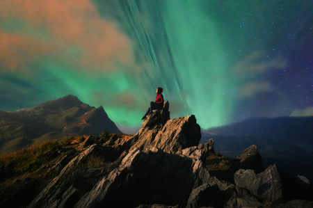 Women tourists sit at the top of the rock with Northern Lights or Aurora Borealis, Beautiful landscape. Фото со стока