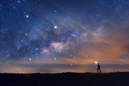 Escalador o mochilero con fuego en la mano en el pico de la montaña rocosa, encuentra el objetivo, busca bajo las estrellas y la Vía Láctea en la noche, éxito o ganador, concepto de líder. Alto iso con ruido. Foto de archivo