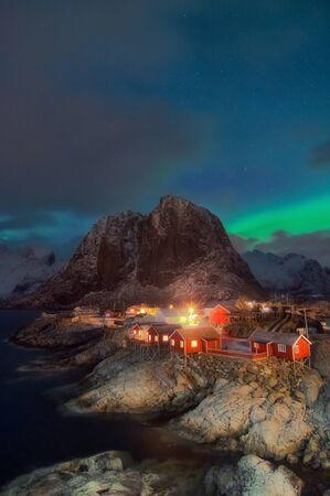 Belle vue sur la cabane de pêche pittoresque de nuit dans le paysage hivernal de l'archipel des îles Lofoten au sommet de la montagne Hamnoy et Lilandstinden, Beau paysage de montagne en hiver Reine Norvège, Scandinavie. Banque d'images