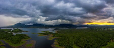 Landscape Aerial view panoramic at sunset with rainstorm above mountain in Mae Chang Reservoir, Mae Moh, Lampang, Thailand, Drone.