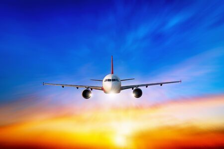 Commercial airplane flying above clouds in dramatic sunset light. Fast Travel and transportation concept, Passenger airplane Travel. Standard-Bild